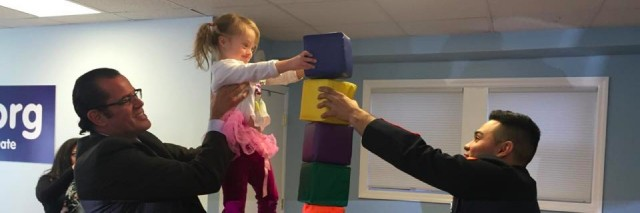 Young girl with a disability stacking blocks with a marine, her dad is lifting her to the top of the stack.