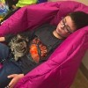 Young boy laying on a beanbag a kitten on a leash is sitting in his lap