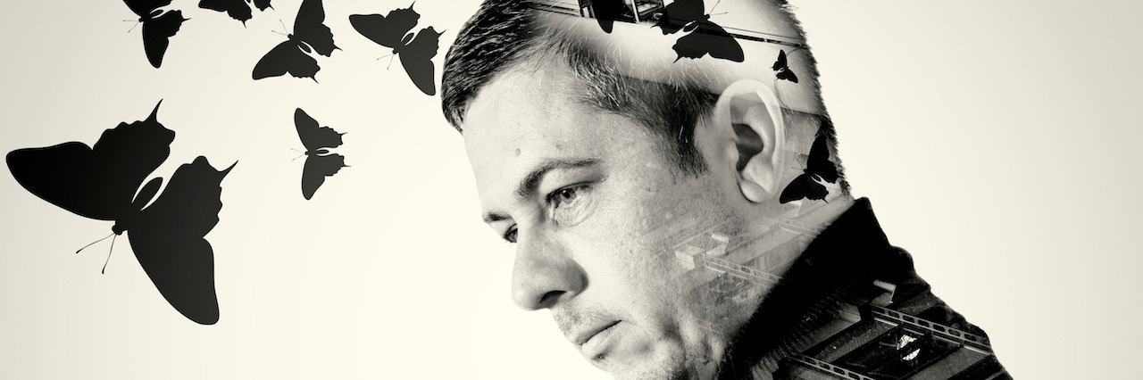 Single man with an industrial background double exposure background on his body with flying butterflies emerging from his head. Black and white monochrome image.