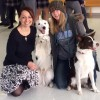 teacher smiles with former student and two dogs