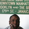 Darius McCollum sitting in front of a sign