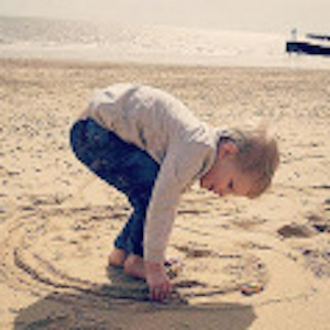 The author's son, drawing in the sand at the beach