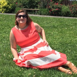 woman in red and white dress sitting on grass lawn