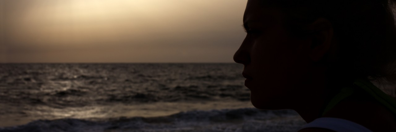 silhouette of girl on sunset beach