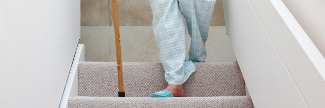 Woman walking down stairs with cane.