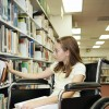 A young teen girl in a wheelchair selecting a book at the library.