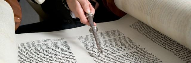 Bar Mitzvah - boy reads Torah scroll.