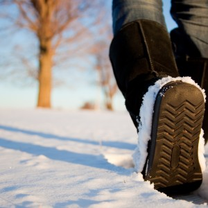person in brown boots walking in the snow