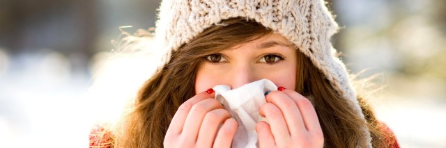 woman wearing a hat outdoors holding a tissue over her nose and mouth