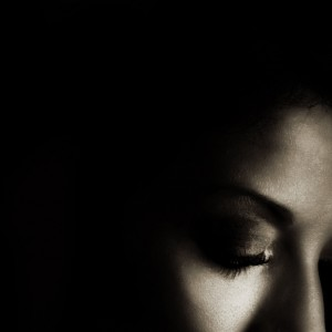 Profile of woman with eyes closed in a dark space