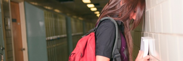 a student with a backpack leaning on a hall in the hallway