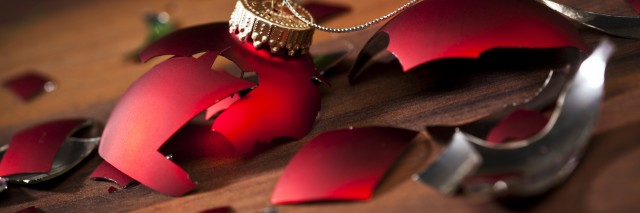 broken red christmas bauble and shards on wooden floor