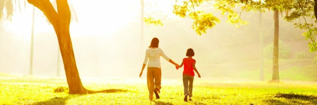 Mother and daughter holding hands, walking through park on sunny day