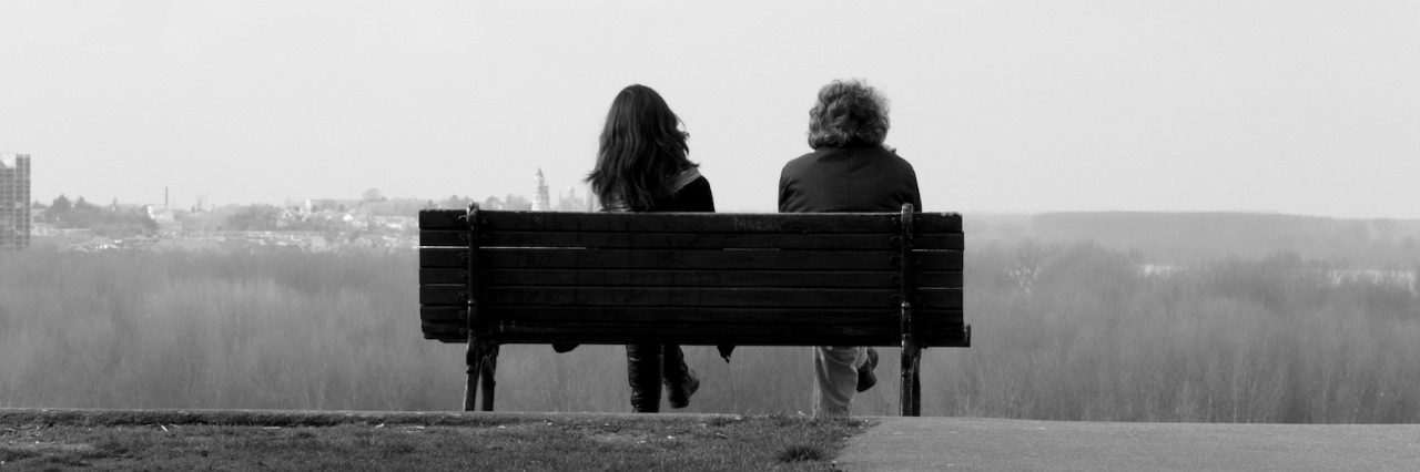Black and white photo of two people sitting on a bench