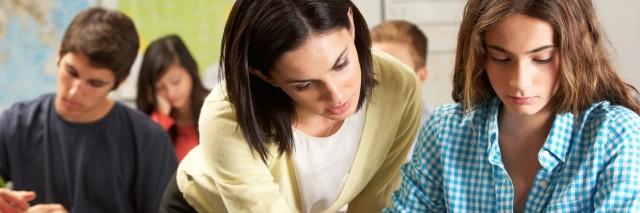 teacher helping female student at her desk
