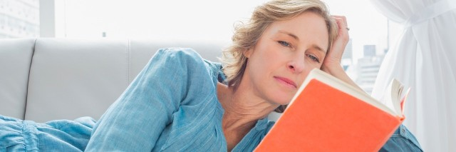 woman reading a book on a couch