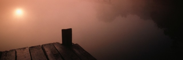a dock looking over a misty lake at sunrise