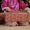 Girl kneeling by Christmas tree, holding present.