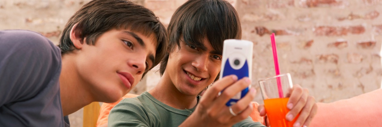 Two teenage boys (14-17) looking at mobile phone