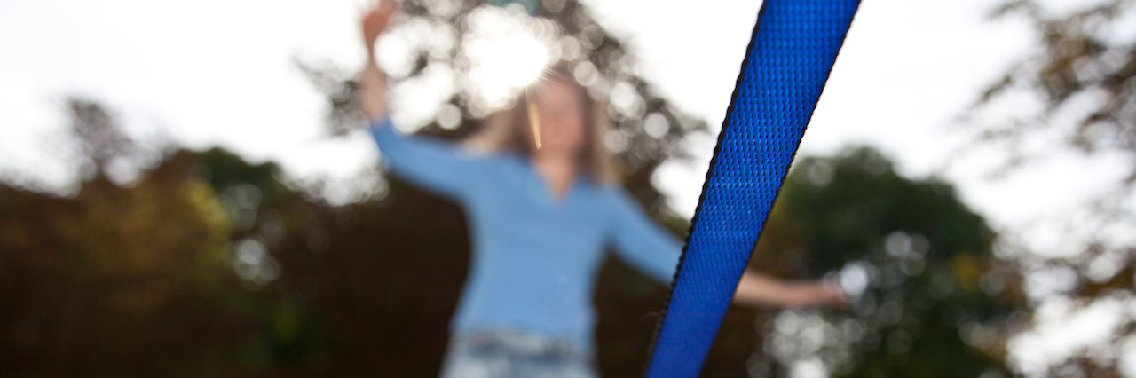 Woman on Slackline in Parc with focus on slack line