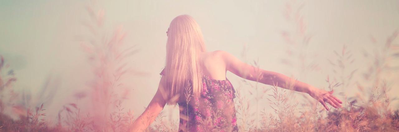 girl walking through field of long grass