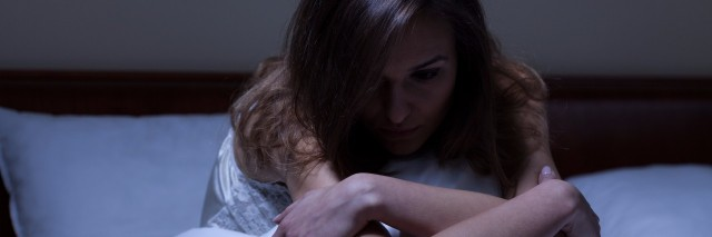 woman siting up in bed at night