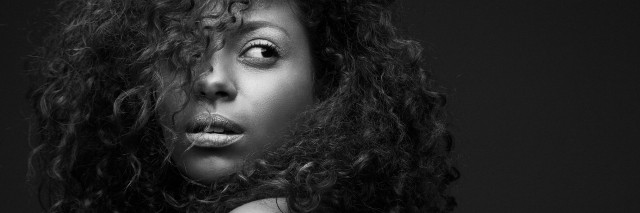 black and white image of woman with dark curly hair looking over her shoulder