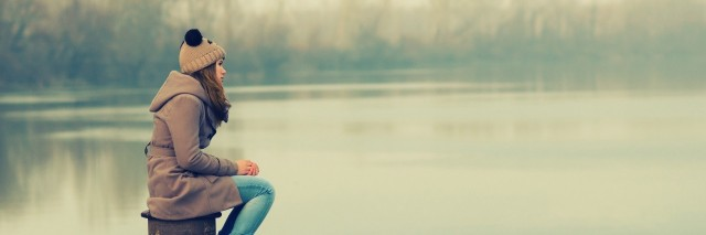 girl sitting on a dock during a gloomy winter day