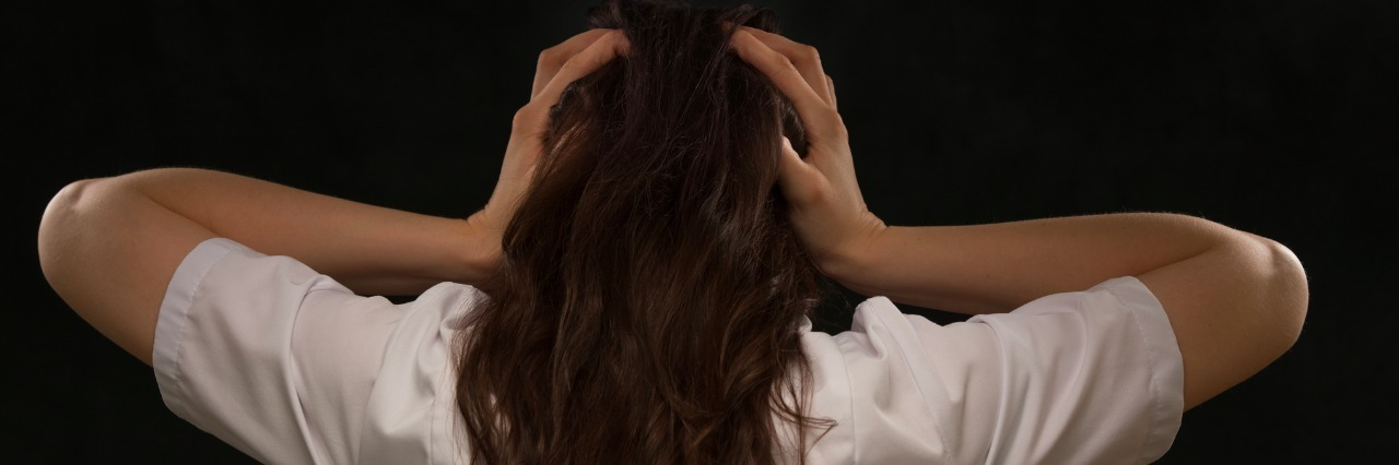 rear view of woman holding her head on black background