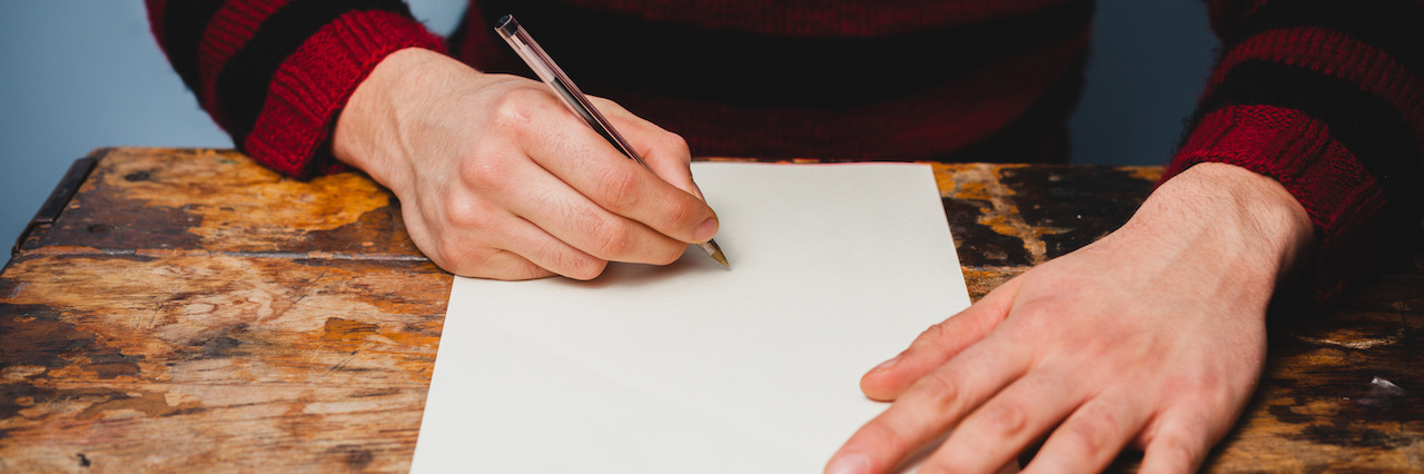 Young man is writing a letter
