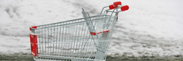 Supermarket shopping cart outside in snow.