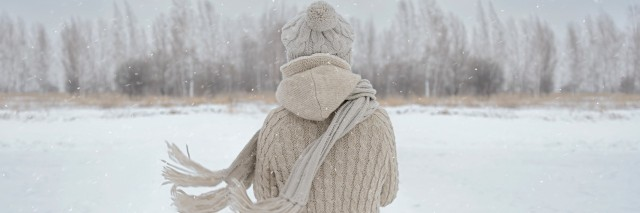 back of woman standing on snowy field