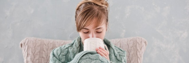 woman wrapped in blanket sipping tea