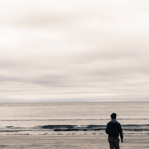 Picture of man from behind walking on a beach