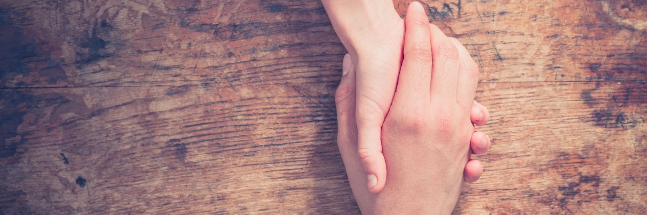 Two people holding hands at a wooden table