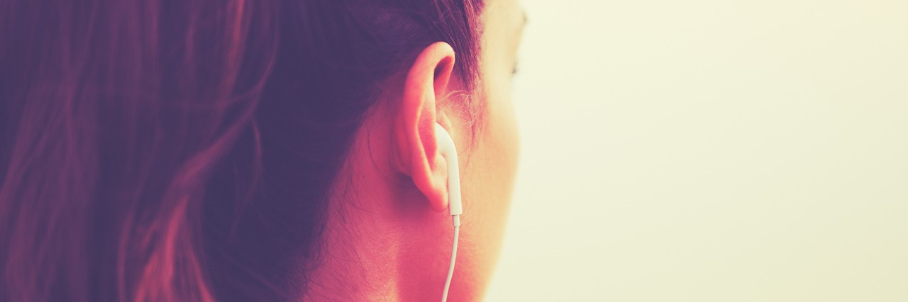 back view of a woman's head with headphones in her ears