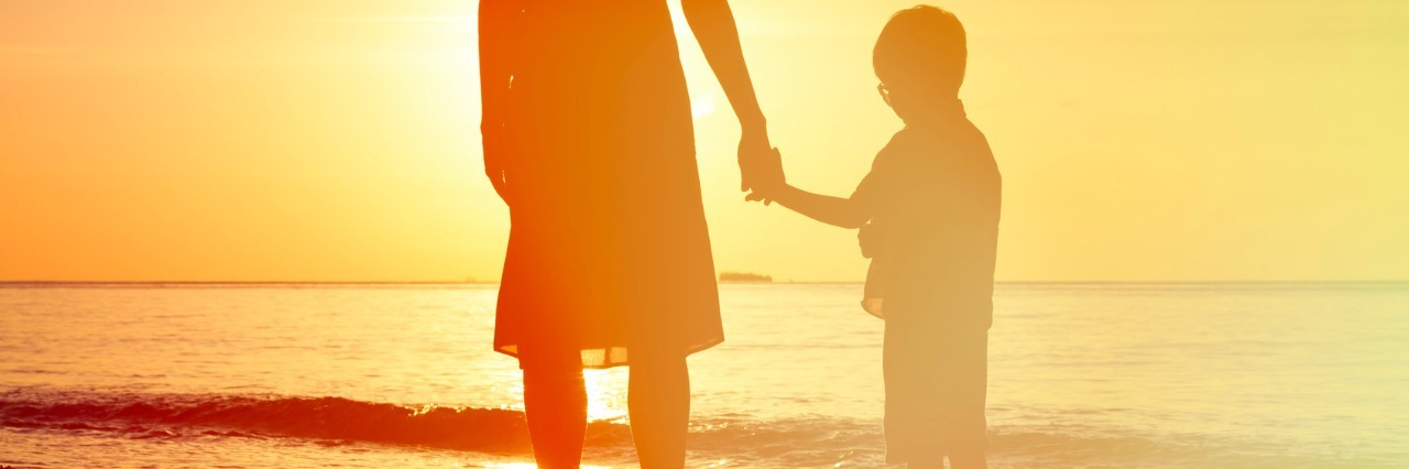 Silhouette of mother and son holding hands and facing the water while standing on the beach