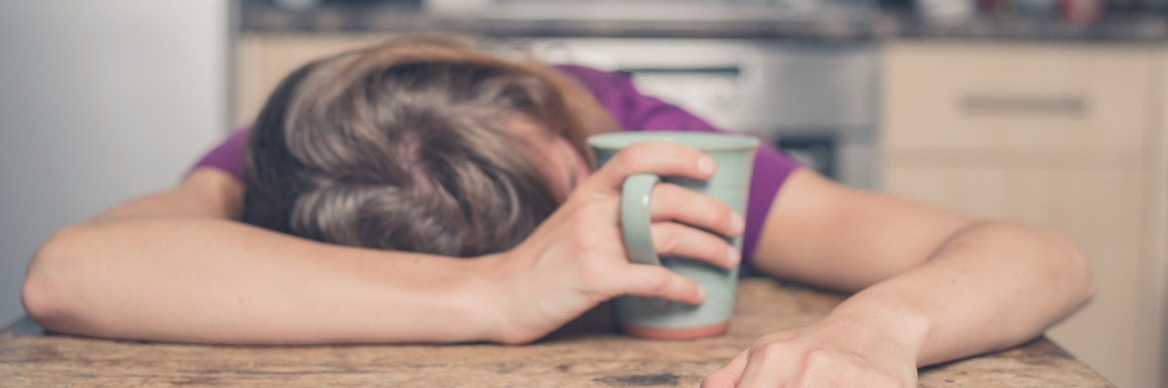 a woman in a purple shirt lays her head on the table while holding a mug of tea
