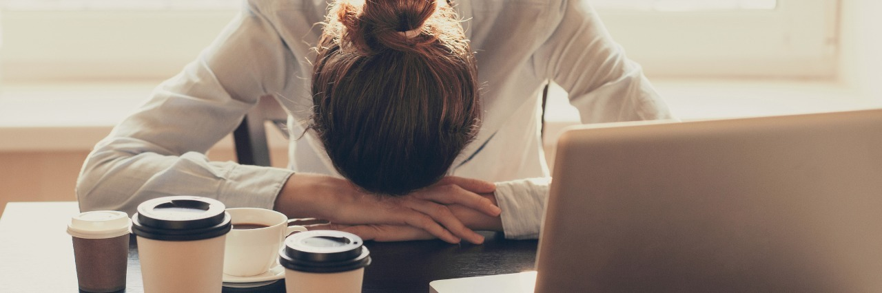 woman with her head down on her desk at work next to her laptop and several cups of coffee