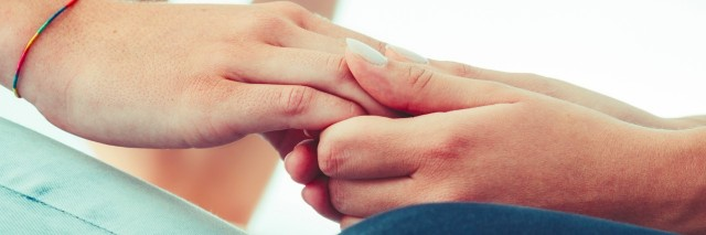 Close-up photo of person holding another person's hands