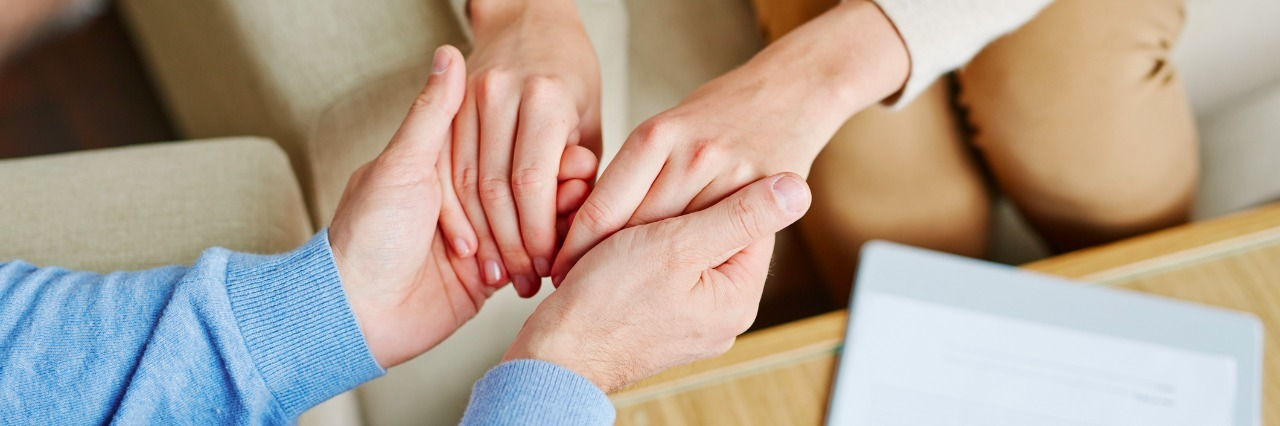 close-up of therapist holding patient hands
