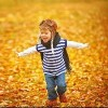 child playing outdoors in pilot outfit among fall leaves