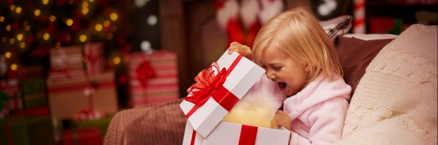 Child opening present on Christmas morning.