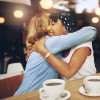two friends hugging while getting coffee