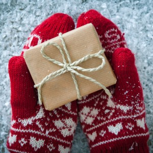 hands wearing festive red and white mittens and holding a small box wrapped in paper and tied with a bow