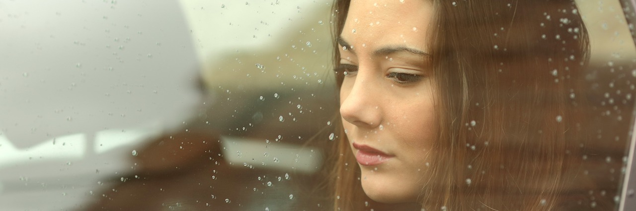a sad young woman sitting in a car on a rainy day