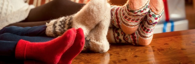three pairs of feet in fuzzy holiday socks resting on a table