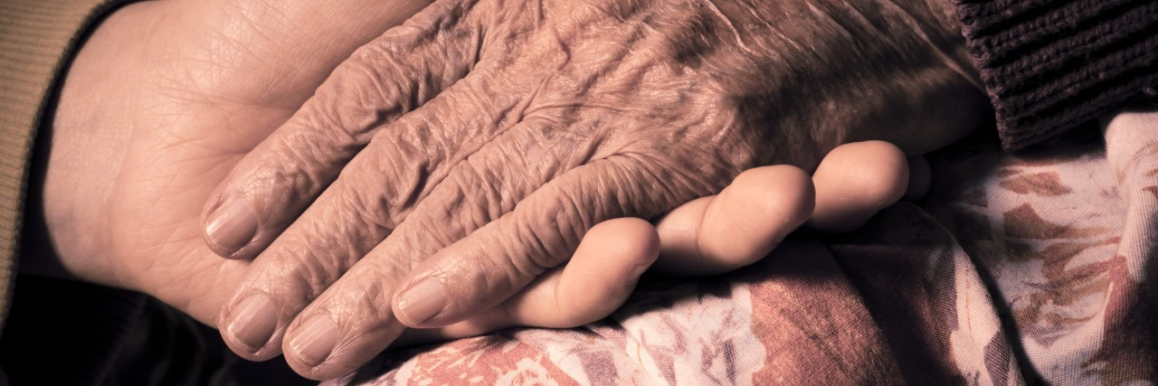 close up of a young woman holding her grandmothers hand on a hospital bed