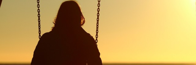 Woman sitting on swing, looking onto the water at sunset