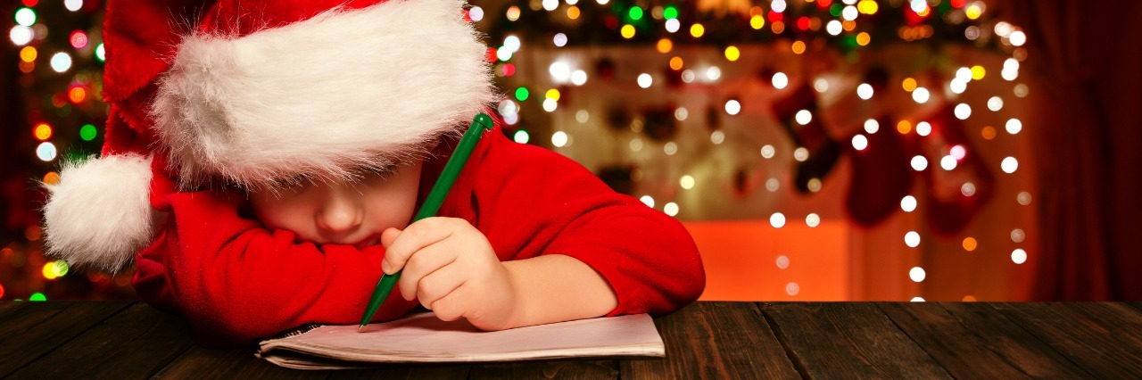 boy in santa hat writes a letter to santa with christmas decorations in the background